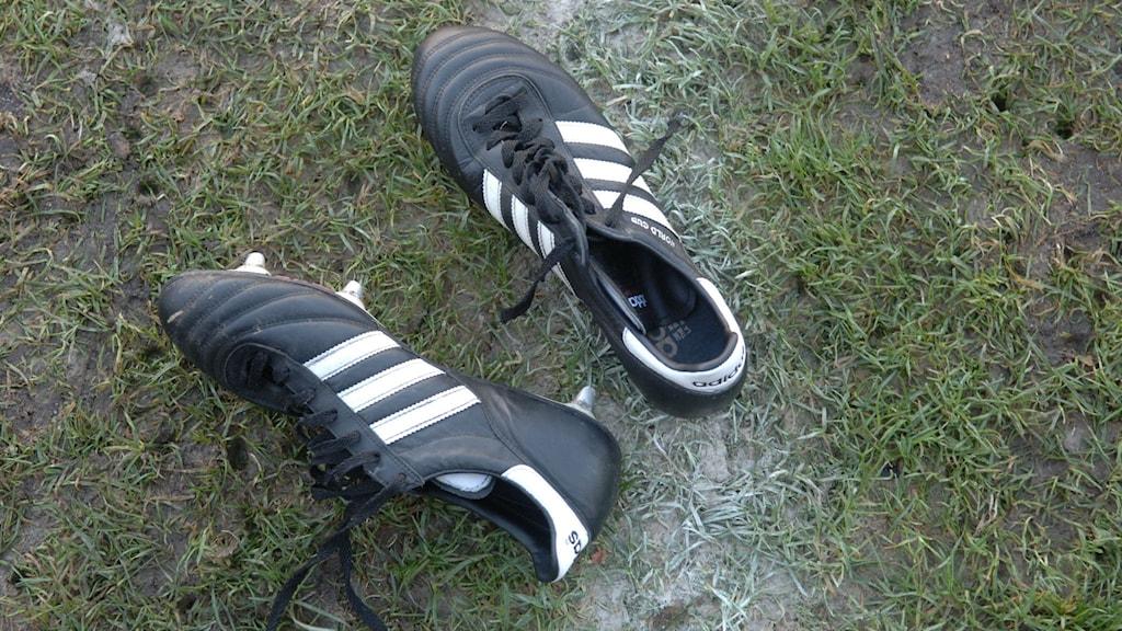 Fotbollsskor på en gräsplan.