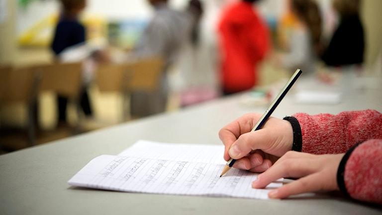 Elev skriver i klassrum. Foto: Jessica Gow/TT.