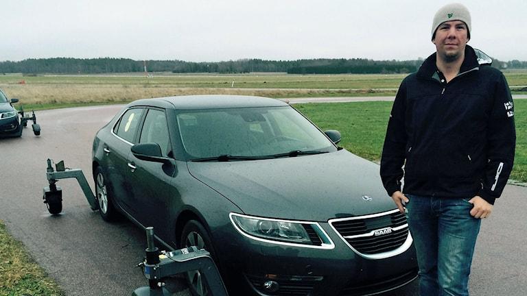 Axel Regin, lärare på Hässlö trafikövningsplats bredvid bil på halkövningsbanan. Foto: Filip Annas.