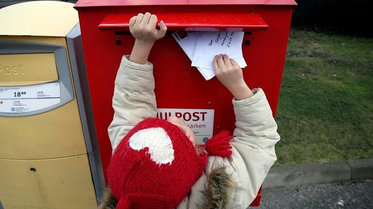 En liten flicka postar julkort i en röd brevlåda avsedd för julpost. Foto Fredrik Sandberg/TT.