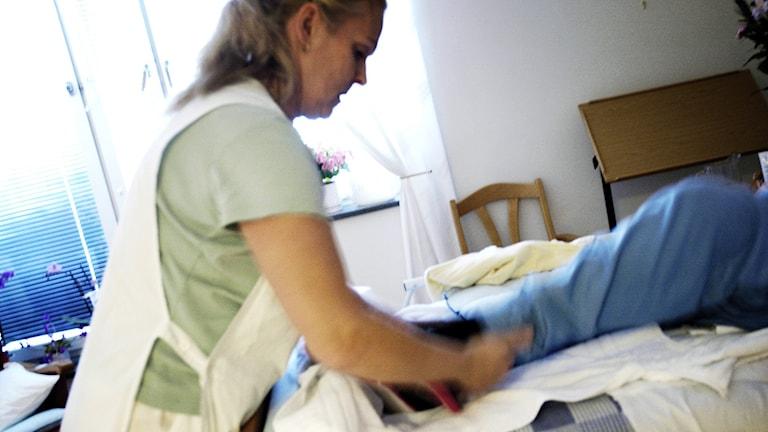 Person som ligger i säng sköts om av personal i kortärmad skjorta och skyddsförkläde. Foto: Nina Varumo/TT.