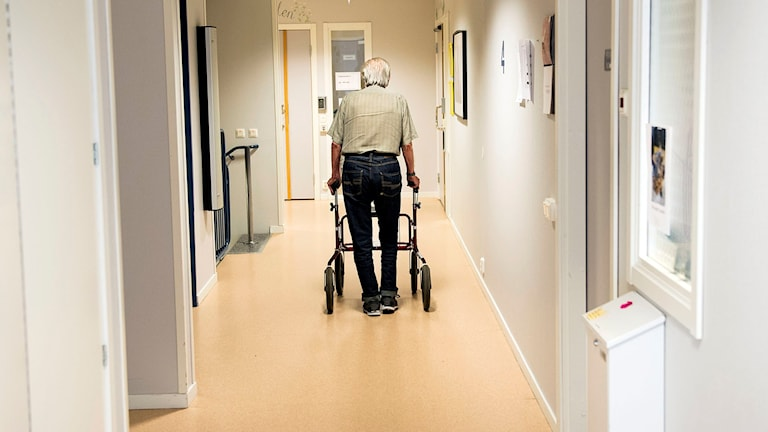 Man går med rullator på ett äldreboende.