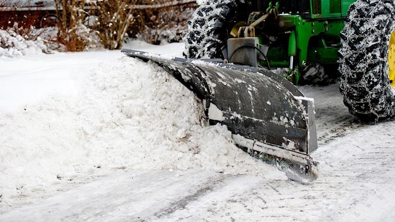 Grön traktor röjer vit snö. Jon Olav Nesvold/TT.