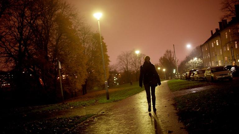 En kvinna går på en gångväg en mörk kväll