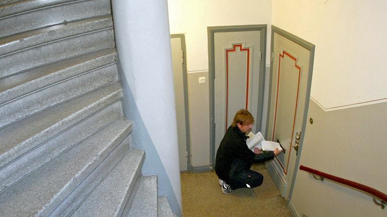 Brevbärare hukar sig för att stoppa in post i ett brevinkast som sitter lågt på dörren.