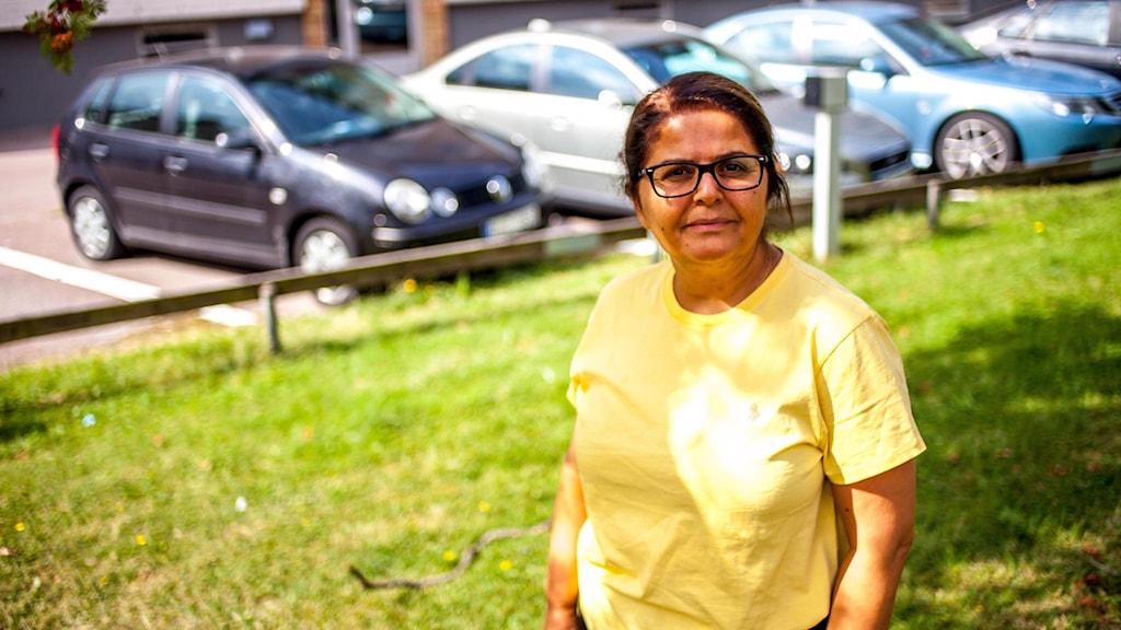 Khadijeh Hassanpour står i naturen, bakom henne kan man se bilar.
