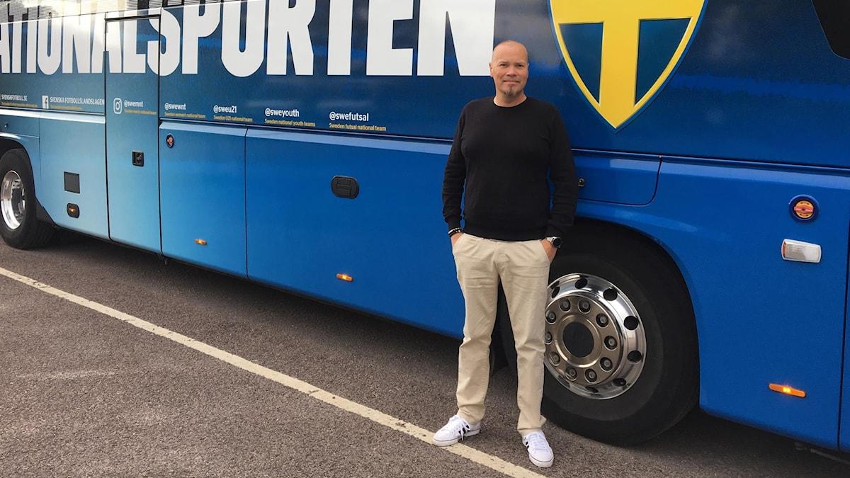 Denny Bauer framför bussen som fotbollslandslagen åker i.