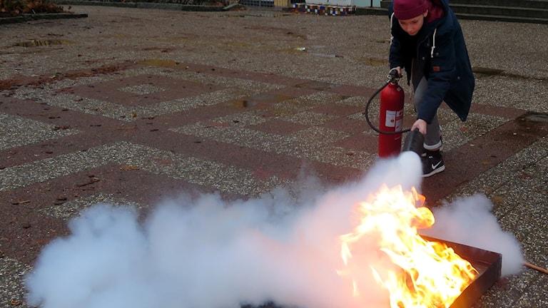 Rasmus Rågberger släcker brand med brandsläckare.