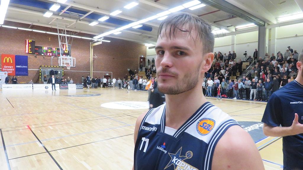 Sean Smith Köping Stars. En svettig spelare mer blå och vit tröja bakom honom en tom basketplan och en fullsatt läktare. Foto: Hans Sjöström.