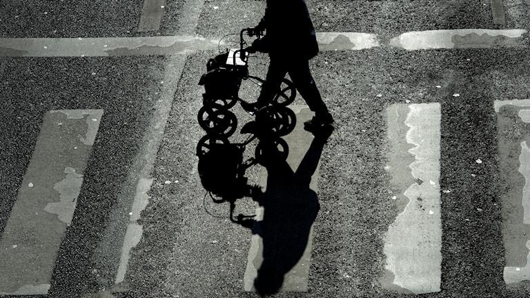 Människa med rollator som går över en gata