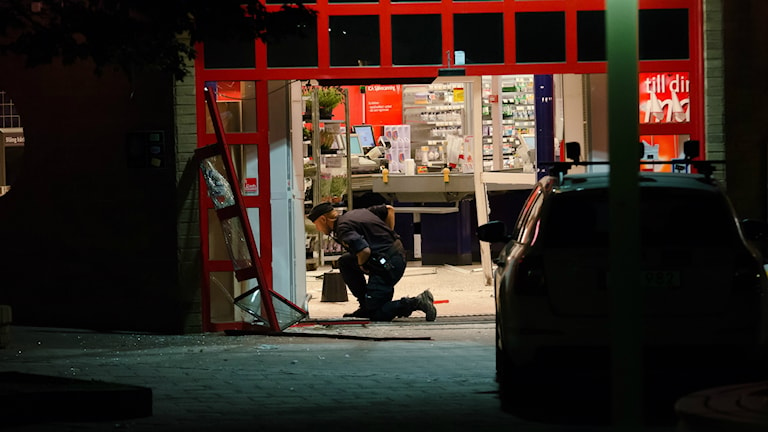 En polis genomför en undersökning av entrén till den rånade mataffären i Hallstahammar.