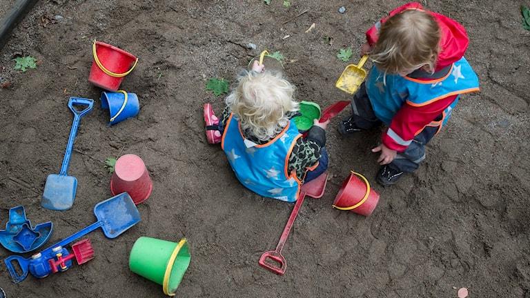 Två barn leker i en sandlåda på en förskola.