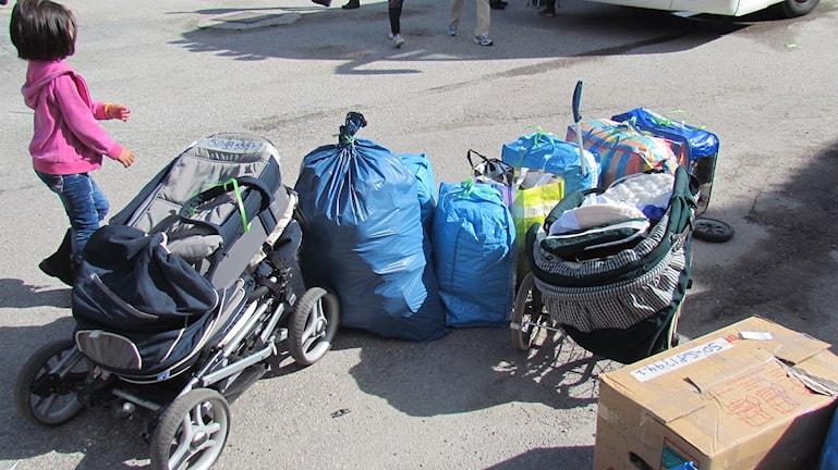Kuvassa on pieni tytto ja erilaisia muovisäkkeihin pakattuja nyssäköitä, joissa on turvapaikanhakijoiden tavaroita. Asylsökandes bagage.