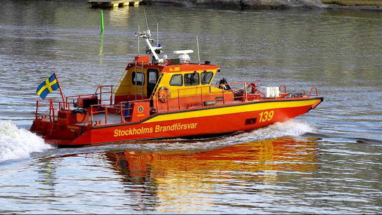 En gul och röd brandbåt på vattnet.