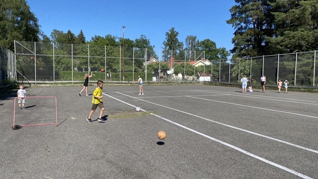 Barn springer runt på tennisplan.