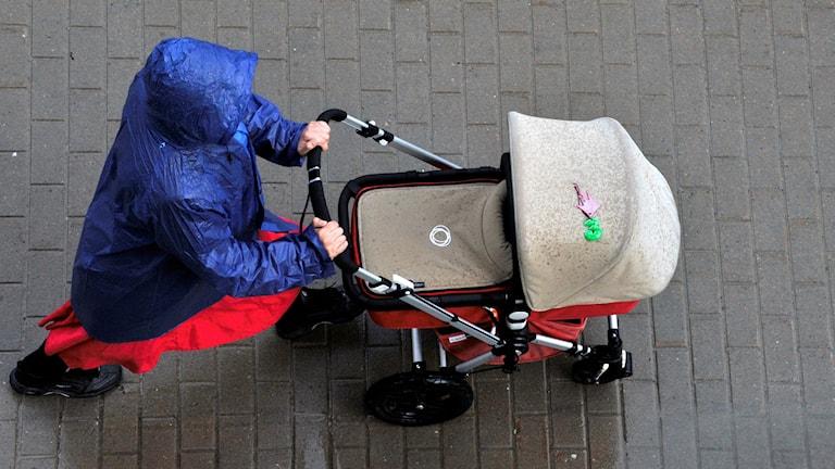 Kvinna med barnvagn.