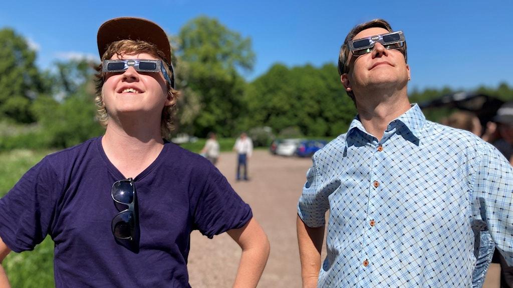 Två killar i skyddsglasögon tittar mot himlen.