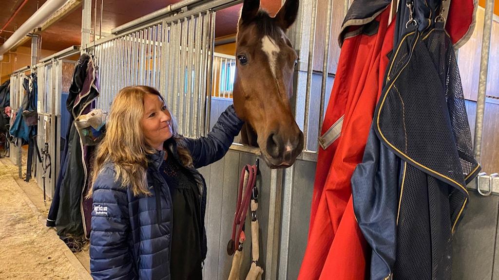Mia Viberg tillsammans med hästar i stall