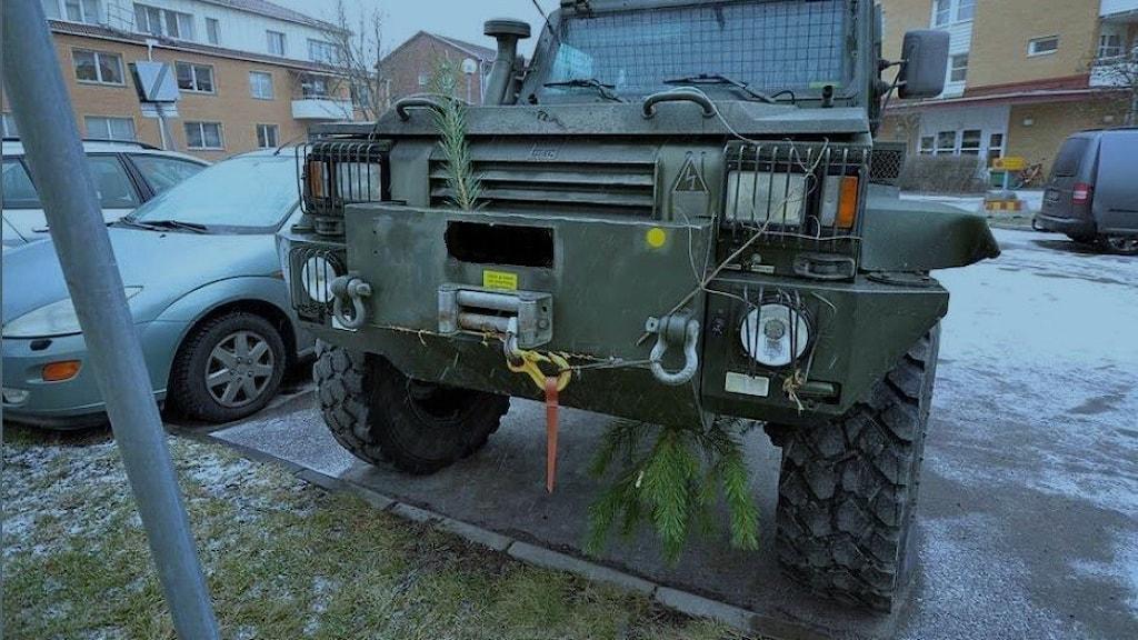 Ett militärfordon står uppställt på en parkeringsplats i ett bostadsområde. I kofångaren hänger en gren.