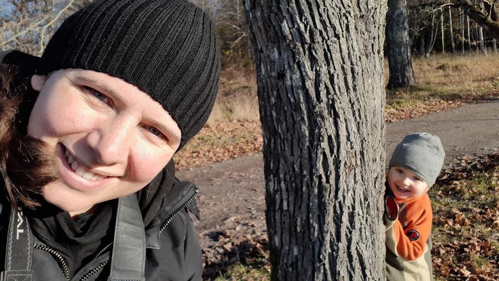 Marléne Tamlin i närbild till vänster medan dottern Althea tittar fram bakom ett träd till höger i bild.