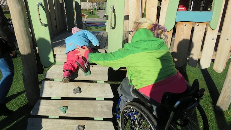 Jessica Zyrenia hjälper sitt barn på lekplatsen vid Nordanby äng.
