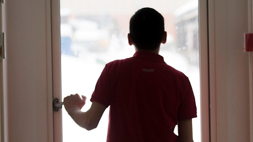Pojke blickar ut genom fönster. Foto: Fredrik Sandberg/TT.