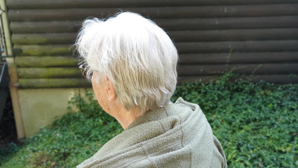 En äldre gråhårig kvinna.