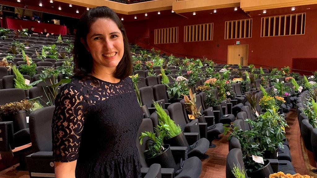 Marisol Taub, produktionskoordinator på konserthuset. Framför en konsertsalong fylld av krukväxter.