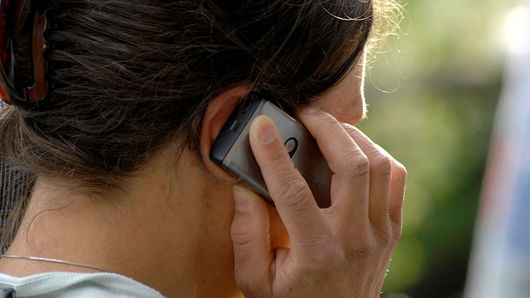 Kvinna talar i en mobiltelefon.
