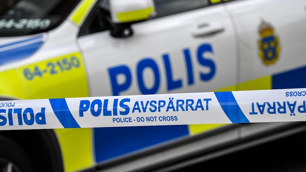 Polisbil vid avspärrningsband.