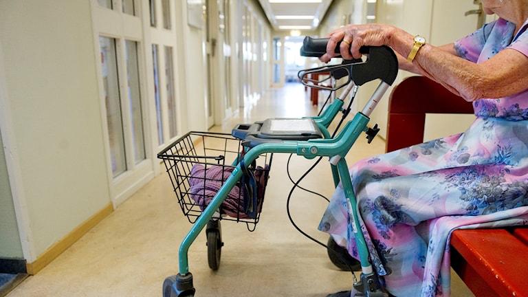 En äldre kvinna med rollator sitter på en bänk i en korridor vid ett äldreboende.