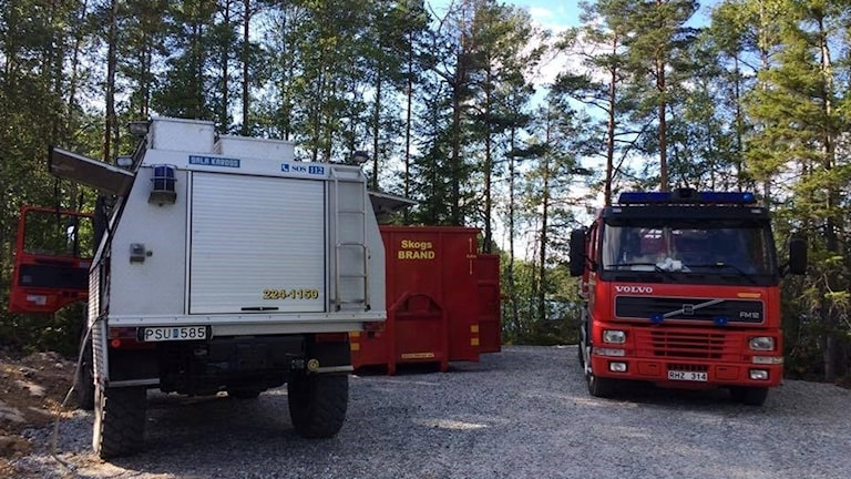 Akrivbild: Brandbilar i skog.