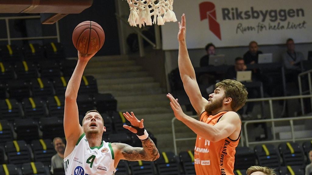 Två basketspelare under en basketkorg