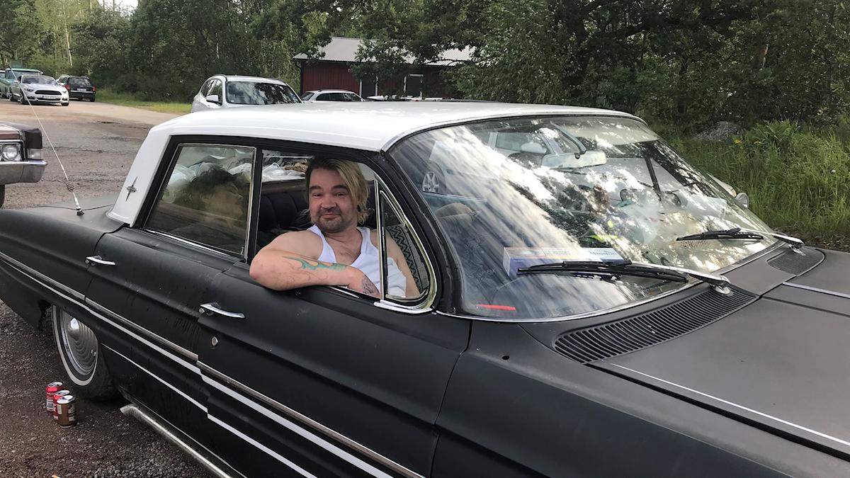 En man i en raggarbil
