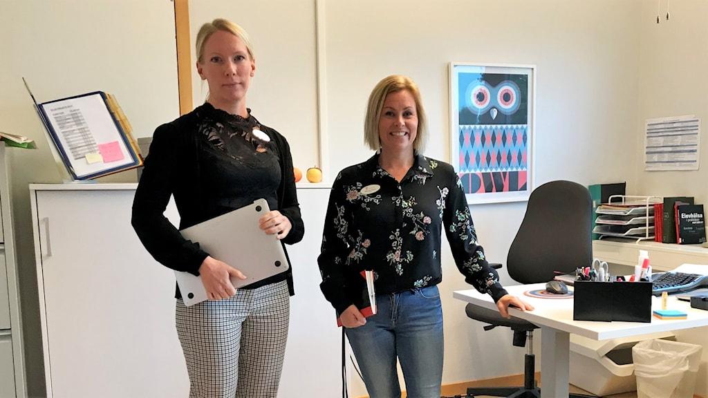 Martina Bodin, specialpedagog och Michaela Eriksson, rektor på Vallbyskolan i Västerås står vid ett skrivbord på rektorns kontor.