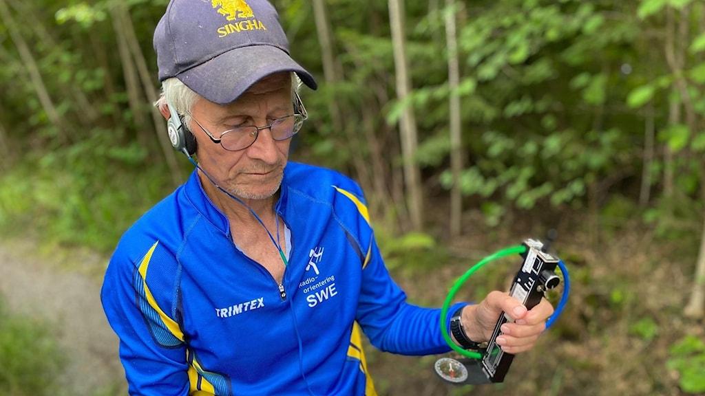 Peter Ljungström från radioklubben med pejlutrustningen i skogen.