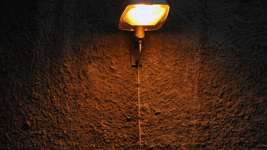 En lampa som lyser i mörkret ute.