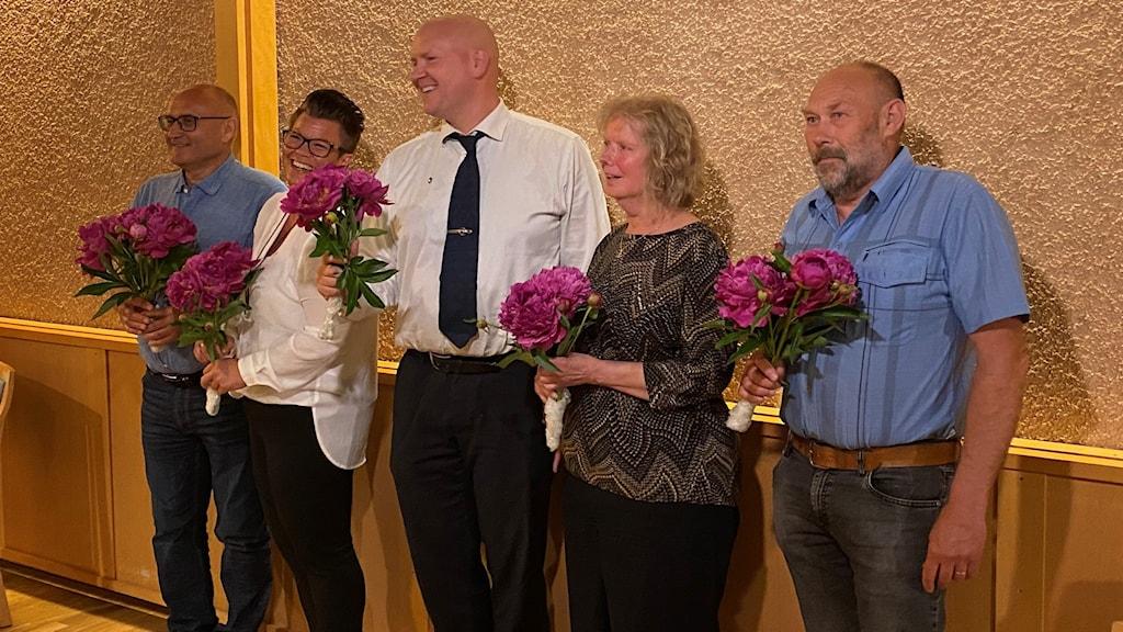 Kvinnliga och manliga politiker med blommor.