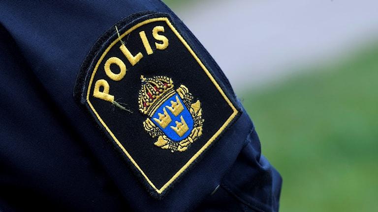 Polissymbol på höger arm på en polisuniform.