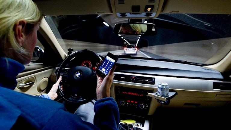 En kvinna knappar på sin mobil samtidigt som hon kör bil.
