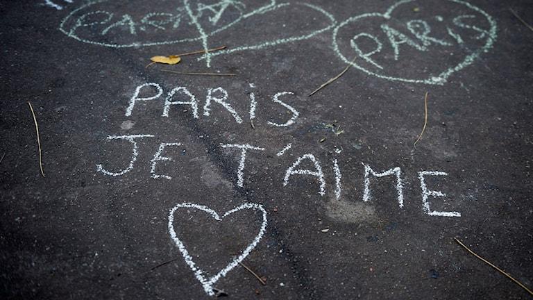 """Bild på hjärtan ritade med krita på marken och textten """"Paris je t'aime""""Foto: Vilhelm Stokstad/TT"""
