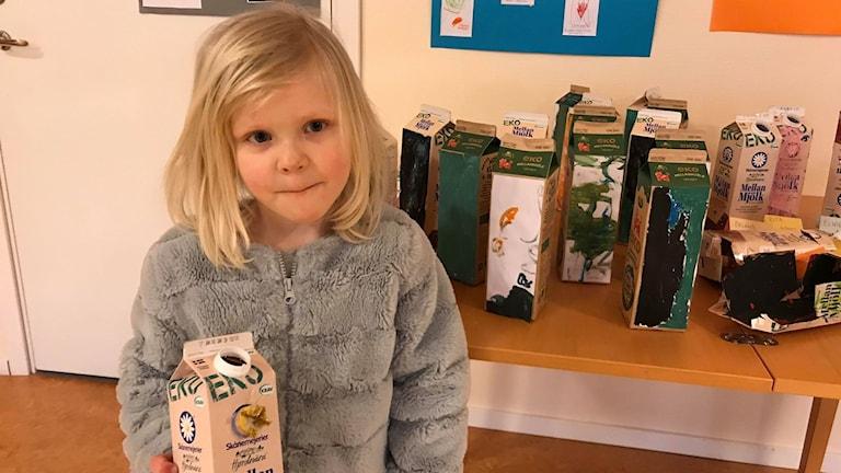 Greta, 5, med sitt återvunna mjölkpaket.