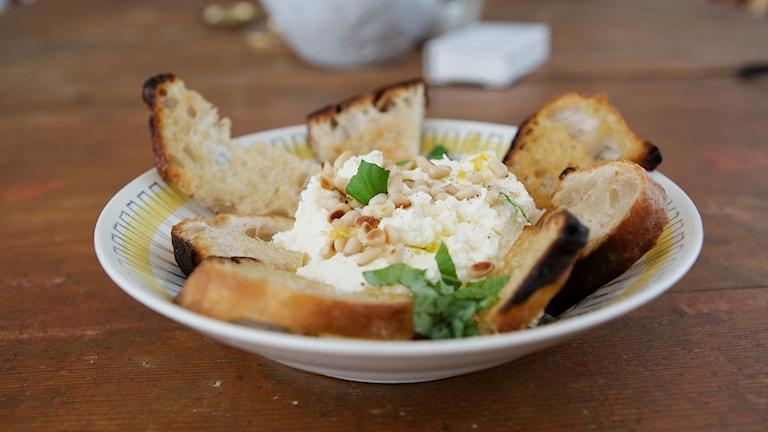 På en tallrik ligger rostat bröd i en ring runt den krämiga fuskburratan som pyntats med basilika, olivolja och citronzest.