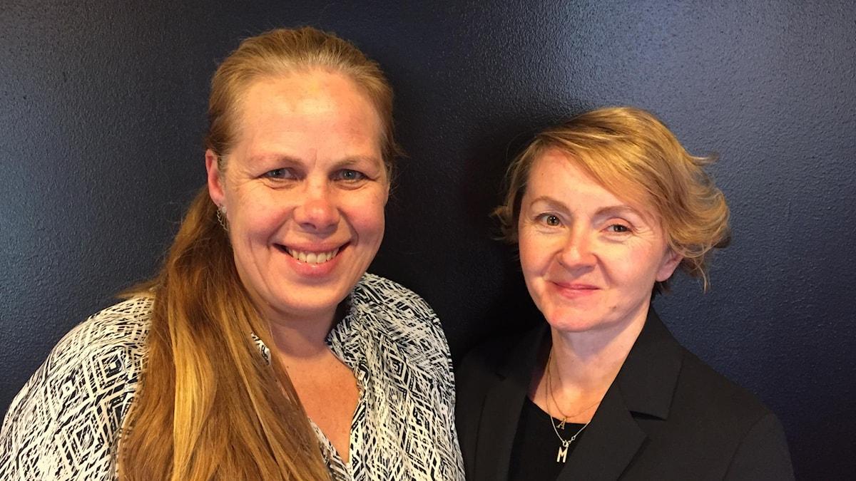 Två blonda kvinnor står framför en svart vägg och ler.