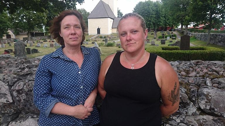 Susanne Hedman & Ann-Christin Zingerman står vid en stenmur. I bakgrunden syns kyrkogården och Husby-Ärlinghundra kyrka.