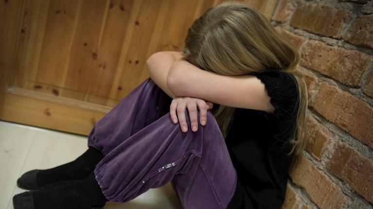 Genrebild på anonym flicka som sitter ner på golvet, ser ledsen ut och och gömmer ansiktet i armarna.