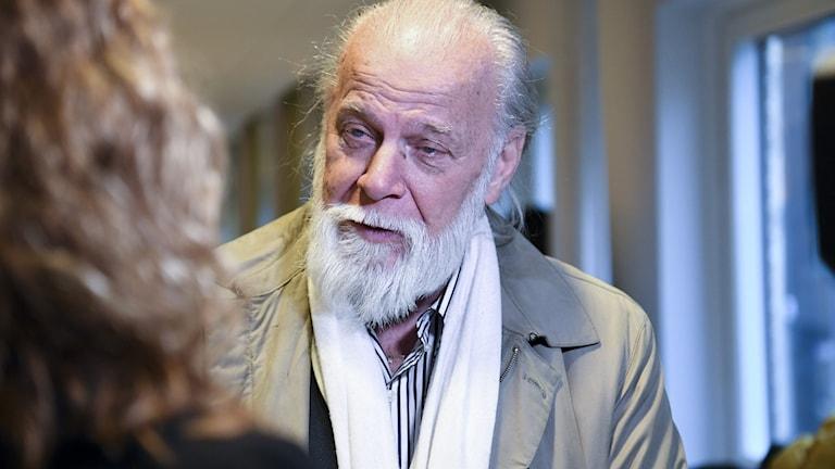 En äldre man med vitt hår och vitt skägg.