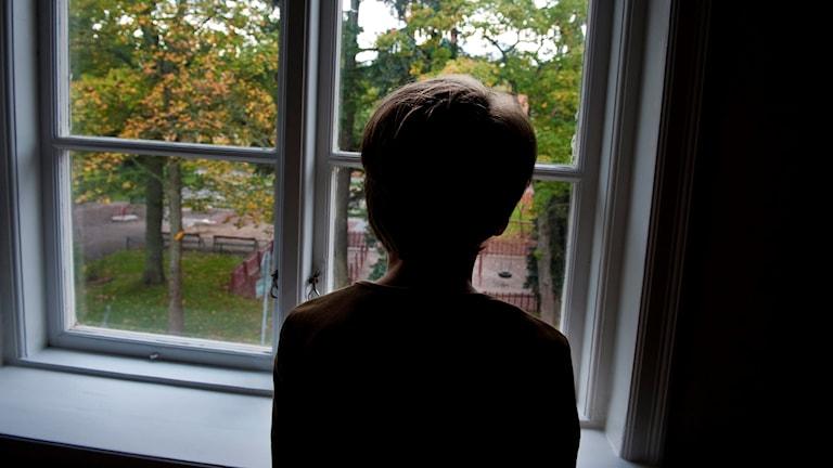 Barn står och tittar ut genom fönster. Genrebild.