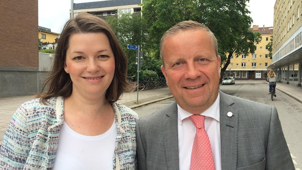 Moderaterna Marta Obminska och Fredrik Ahlstedt står bredvid varandra på en gata, ler och tittar in i kameran.