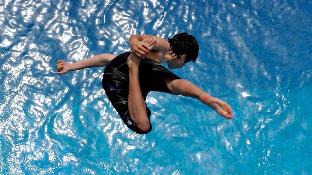 Pojke hoppar ner i bassäng. Foto: Dominic Favre / Scanpix